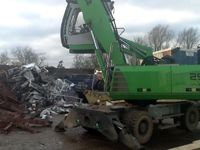 Excavator collecting scrap metal